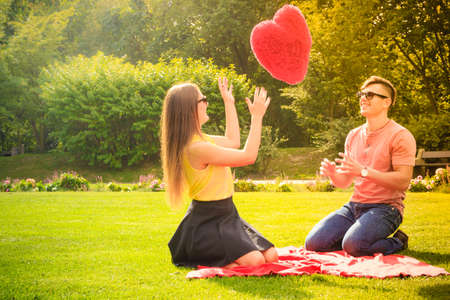 young at heart: Love and dating. Young fashionable couple lovers having fun with big red heart in park. Picnic concept