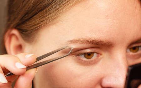 tweezing: Woman plucking eyebrows depilating with tweezers closeup part of face. Girl tweezing eyebrows.