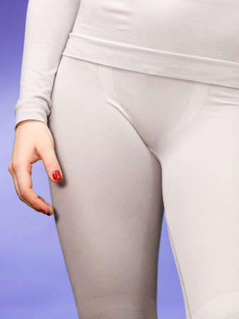 fit girl: Fit woman wearing hot gray sports thermolinen underwear, closeup part of body, studio shot on violet. Long sleeves top and leggings.