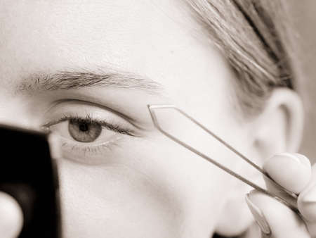 depilate: Woman plucking eyebrows depilating with tweezers closeup part of face. Girl tweezing eyebrows, black & white photo