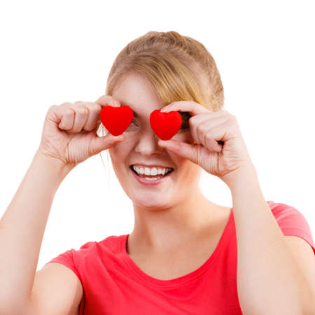 emotional love: Smiling funny playful girl holding red hearts over eyes. Valentines day love happiness concept. Stock Photo