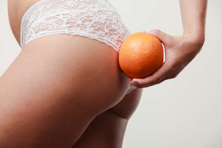 with orange and white body: Absence of cellulite. Part body of slim fit girl holding orange next to the bottom buttocks. Woman wearing white lacy lingerie. Diet aspects. Stock Photo