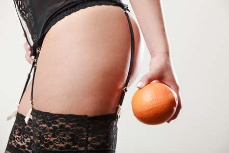 absence: Absence of cellulite. Part body of slim fit girl holding orange next to the bottom buttocks. Woman wearing black lacy lingerie. Diet aspects.