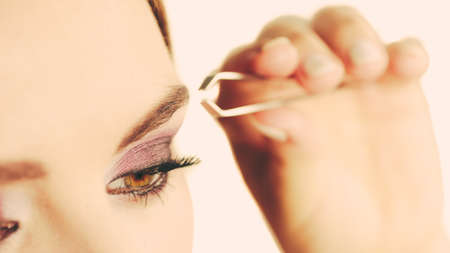 depilate: Make up and cosmetics. Woman plucking eyebrows depilating with tweezers. Attractive girl tweezing eyebrows