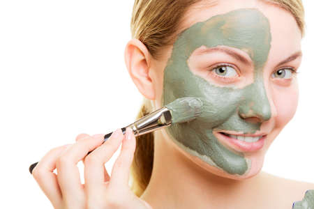 mud girl: Skin care. Woman applying with brush clay mud mask on face isolated. Girl taking care of dry complexion. Beauty treatment.