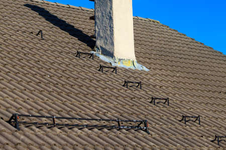 ladder safety: The roofing tiles house roof with chimney and safety metal ladder to climb sky background Stock Photo