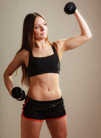 sports bra: Bodybuilding. Strong fit woman exercising with dumbbells. Muscular long hair girl lifting weights