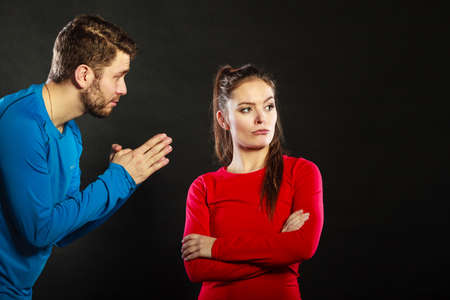 conflicted: Husband apologizing upset angry wife. Man asking woman for forgivness. Boyfriend trying to convince girlfriend. Conflicted couple in studio on black. Relationship problem.
