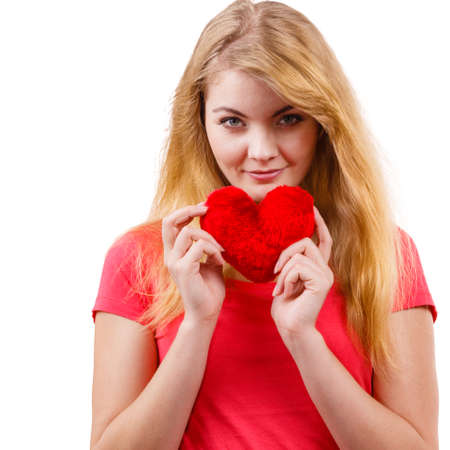 teen love: Woman blonde long hair girl holding red heart love symbol studio shot isolated on white. Valentines day happiness concept