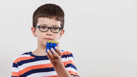 Portret van slimme schattige jongen kleine jongen in glazen met magische Rubik kubus. Onderwijs.