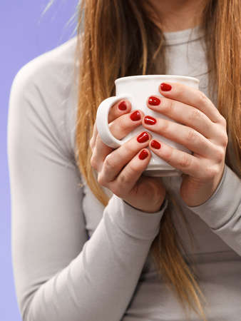 hot drinks: Woman in winter gray sports thermal underwear for skiing training holds mug with tea or coffee warming herself studio shot on violet. Stock Photo