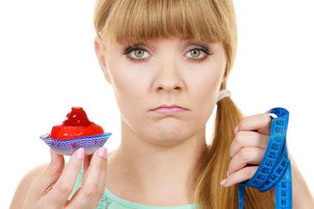 temptation: Woman undecided with blue measuring tape holds in hand cake cupcake, trying to resist temptation. Weight loss diet dilemma gluttony concept. Stock Photo