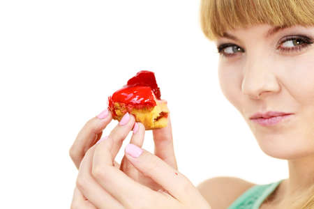 indulging: Woman holds cake cupcake in hand taking a huge bite out of dessert, eating unhealthy junk food. Sweetness indulging and fattening concept Stock Photo