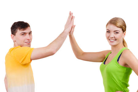 high: Couple fit athletes woman and man having fun. Cheering celebrating excited fitness couple happy and joyful giving high five in celebration. Stock Photo