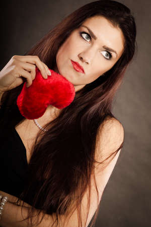 heartbroken: Woman brunette long hair girl wearing black dress holding red heart love symbol studio shot on dark. Heartbroken young female. Sad unhappy face expression