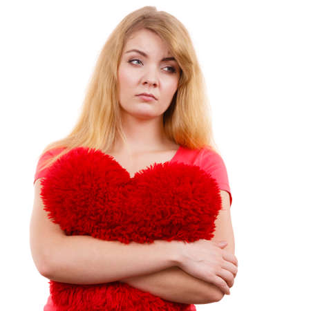 lost love: Woman blonde sad unhappy girl hugging red heart shaped big pillow studio shot on white. Heartbroken young female. Stock Photo