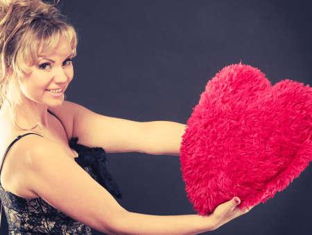 beloved: Woman mid age blonde female elegant evening dress holding big red heart love symbol studio shot on black. Valentines day happiness concept