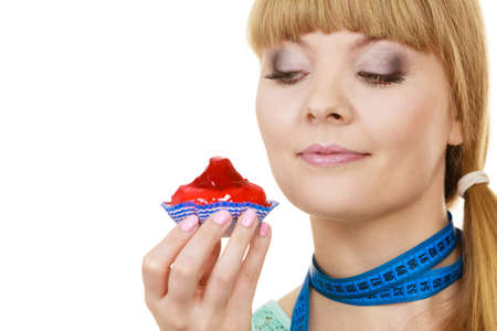 Woman undecided with blue measuring tape around her neck holds in hand cake cupcake, trying to resist temptation. Weight loss diet dilemma gluttony concept.