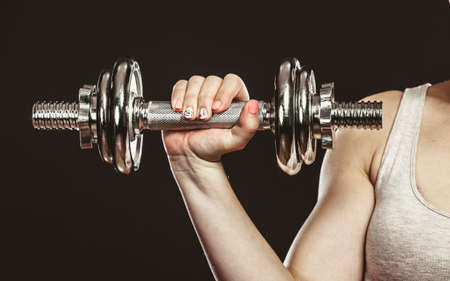 gaining: Closeup of arm hand strong woman lifting dumbbells weights. Fit girl exercising gaining building muscles. Fitness and bodybuilding.
