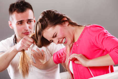 Husband abusing wife pulling her hair. Afraid and scared woman screaming, shouting and crying. Domestic violence aggression. Stock Photo