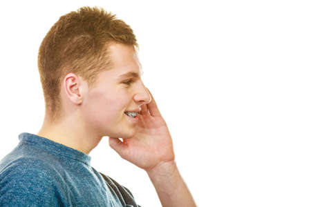 Verbreiten Sie das Wort Thema Klatsch. Junger Mann Gesicht Profil mit Handgeste Sprechen, Flüstern isoliert auf weißem Hintergrund
