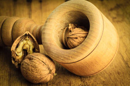 omega3: Healthy food full of omega-3 fatty acids, organic nutrition. Closeup walnut and nutcracker on rustic old wooden table Stock Photo