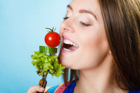 slim woman: Dieting, healthcare and weight loss concept. Sporty girl fitness woman with measuring tape on neck and holding fork with fresh mixed vegetables on blue background. Studio shot.