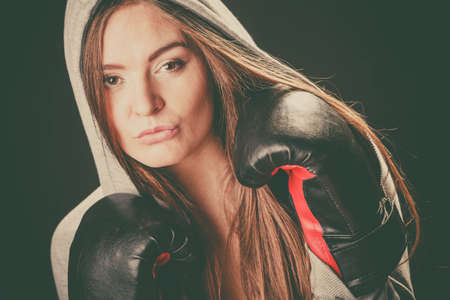 Boxing and feminity. Sport woman hooded with black box gloves