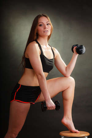 girl bra: Bodybuilding. Strong fit woman exercising with dumbbells. Muscular long hair girl lifting weights on black