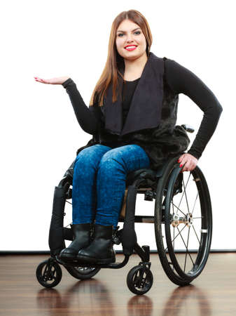 handicap people: Real people, disability and handicap concept. Teen girl unrecognizable person sitting on wheelchair holds open hand for product studio shot on white