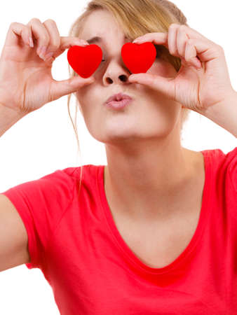 Smiling funny playful girl holding red hearts over eyes. Valentines day love happiness concept. Stock Photo