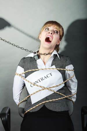 bound woman: Scared businesswoman bound by contract terms and conditions.  Afraid and helpless woman tied to chair become slave. Human hand hold chain and has power over girl. Business and law concept. Stock Photo