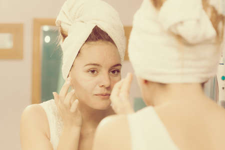 dry skin: Woman applying mask moisturizing skin cream on face looking in bathroom mirror. Girl taking care of her complexion layering moisturizer. Skincare spa treatment.