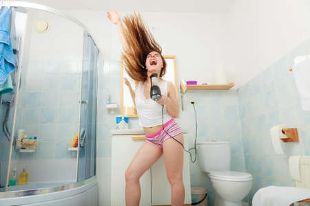 blow dry: Haircare. Beautiful long haired woman drying hair in bathroom Stock Photo