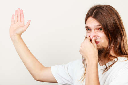 yuck: Expression of very bad smell. Young long haired sweaty man making hand gesture. Sweating concept.