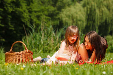 family picnic: Summer children and happy family concept. Mother and daughter little girl having picnic playing in park outdoors. Stock Photo