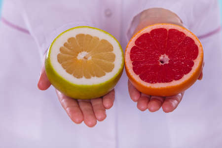 promoting: Person human holding grapefruits in hands promoting healthy food fruit. Right eating nutrition and slimming concept. Stock Photo