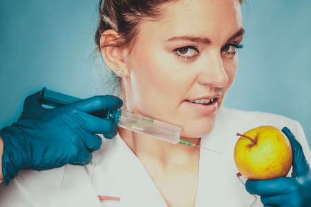modified: Scientist doctor injecting apple with syringe. Woman chemist holding genetically modified fruit. GM food modification.
