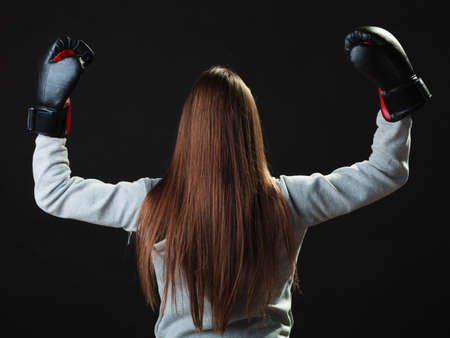 self defence: Martial arts or self defence concept. Sport boxer woman in gloves. Fitness girl training kick boxing back view on black background