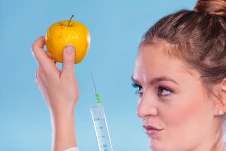 genetically: Scientist doctor injecting apple with syringe. Woman chemist holding genetically modified fruit. GM food modification.