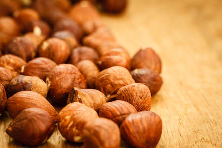 acids: Healthy food full of fatty acids, organic nutrition. Hazelnuts kernel on rustic old wooden table Stock Photo