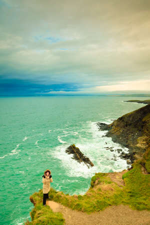 co cork: Irish atlantic coast. Woman tourist standing on rock cliff by the ocean Co. Cork Ireland Europe. Beautiful sea landscape beauty in nature.