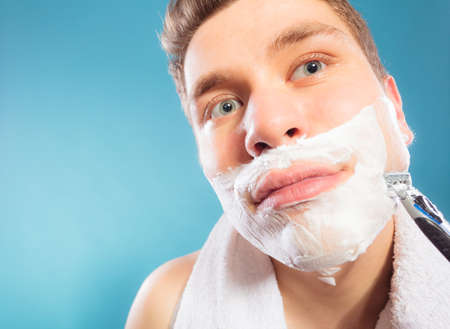 removing: Man shaving using razor with cream foam. Handsome guy removing face beard hair. Skin care and hygiene.