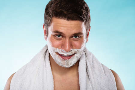 shaving cream: Young man with shaving cream foam and white towel. Handsome guy preparing to shave. Skin care and hygiene.