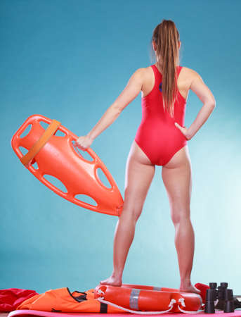 float tube: Lifeguard with rescue tube buoy. Woman supervising swimming pool water. Accident prevention and rescue. Rear back view.