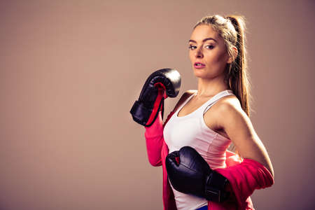 emancipation: Feminist and emancipation idea. Woman in male occupation, training, boxing. Fit female fitness girl doing exercise in studio. Retro and vintage photo.
