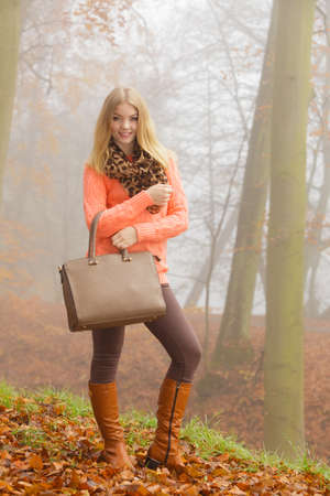 Happy fashionable woman walking in foggy autumn park. Pretty joyful young girl in sweater pullover with handbag in forest. Fall fashion vogue. Stock Photo