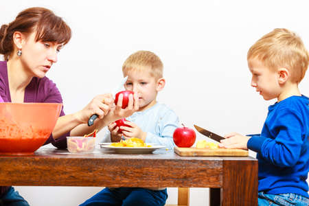 upbringing: Family upbringing childhood concept. Mother and sons boys childs with kitchen knife cutting fruits apples at home. Helping with housework. Stock Photo