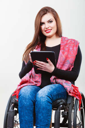 handicap people: Real people, disability and handicap concept. Teen girl unrecognizable person sitting on wheelchair using tablet computer networking, studio shot on gray