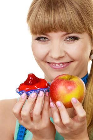 healthy foods: Woman with measuring tape holds in hand cake and apple fruit choosing, trying to resist temptation, make the right dietary choice. Weight loss diet dilemma gluttony concept. Isolated on white